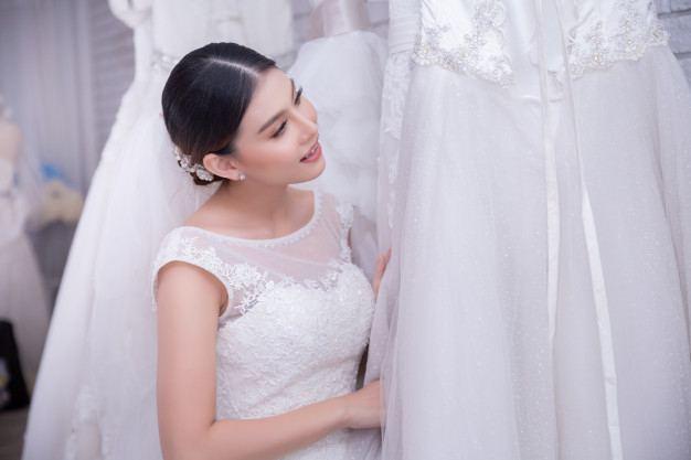 Beautiful bride posing with groom in her wedding day, pretty girl in a wedding dress